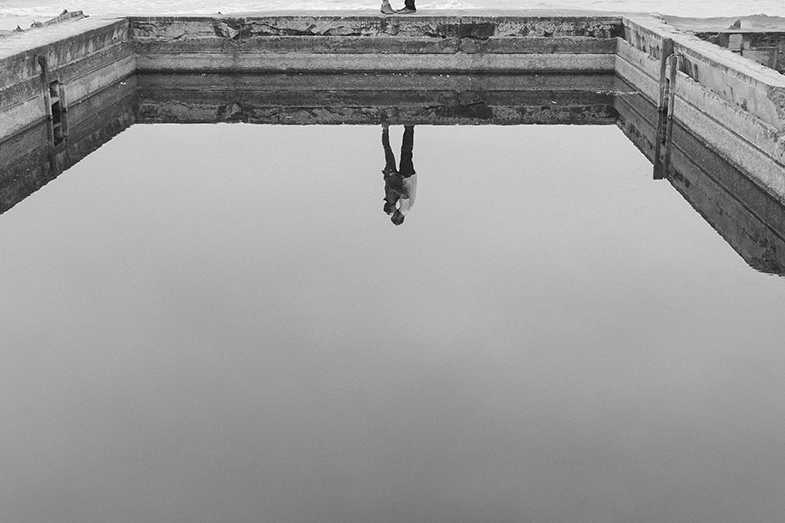 The engaged couple embrace and are reflected in the still water of Sutro Baths in San Francisco.