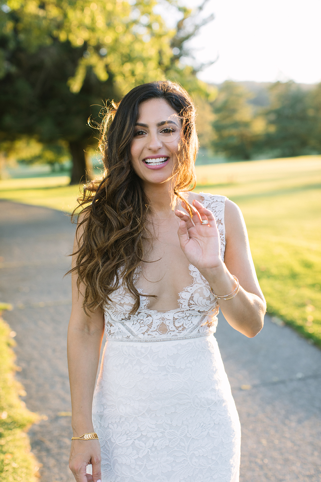 A beautiful bride at sunset smiling while wind blows her hair.