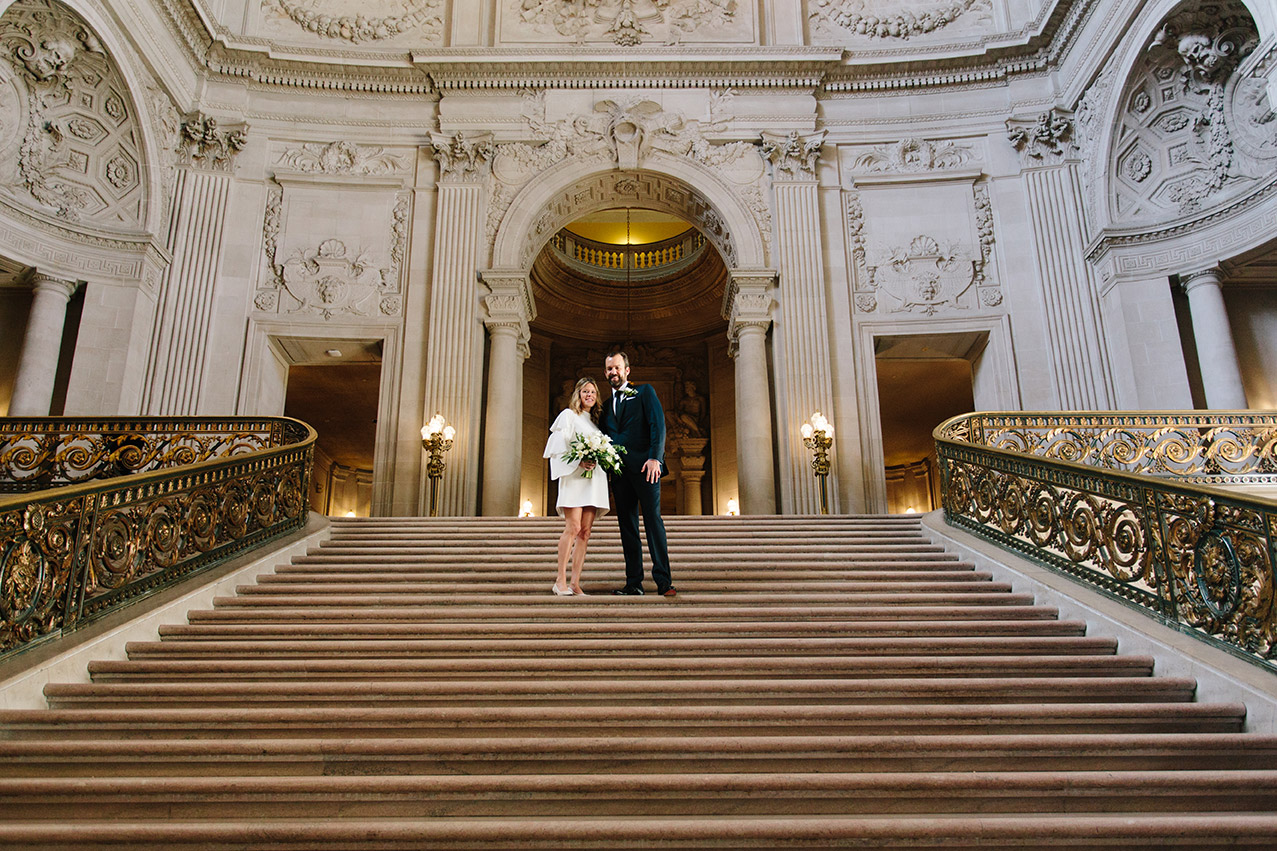 A bride and groom standing on the Grand Staircase at San Francisco City Hall
