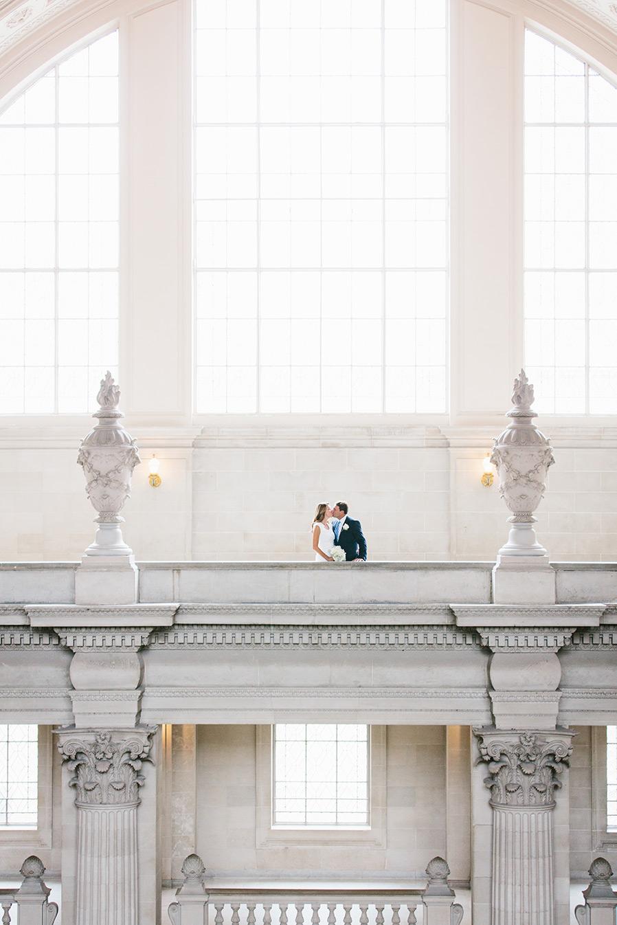 A wedding couple share a kiss on the fourth floor balcony.