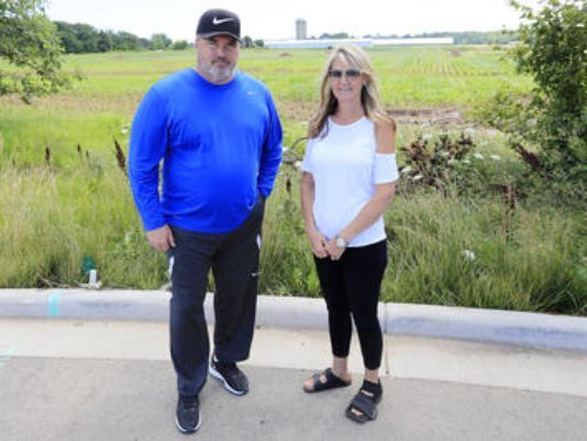 Ledgeview residents Mike McCarthy and Charity Schneider stand at the end of a cul-de-sac in their neighborhood next to a farmland where construction of a manure pit is being proposed..