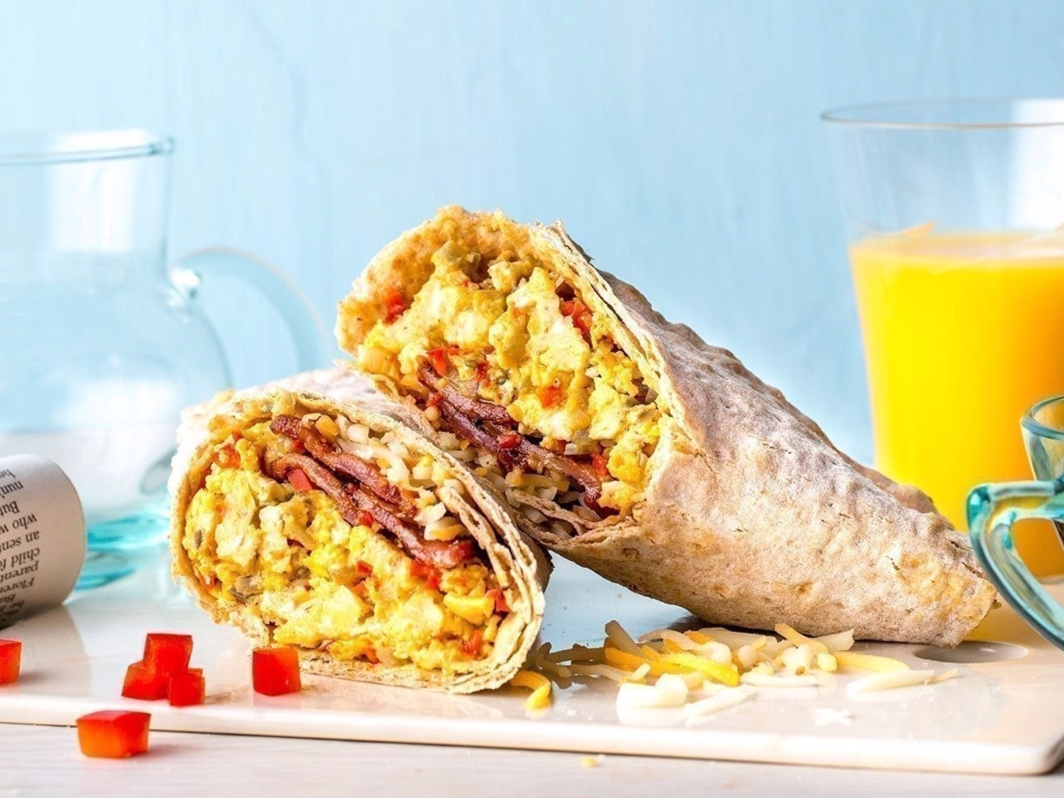 Protein-Packed Breakfast Burritos   Ingredients  8 large eggs  2 tablespoons (30 ml) 2% milk  1 tablespoon (15 ml) olive oil  1 tablespoon (15 ml) minced garlic  1 red bell pepper, minced  1/2 red onion, minced  4 slices thick-cut bacon, cooked until crispy  Salt and pepper  4 multigrain flatbreads  1/2 cup (60 grams) shredded Mexican blend cheese  Calories: 371 Fat: 22g Carbohydrate: 21g Protein: 27g