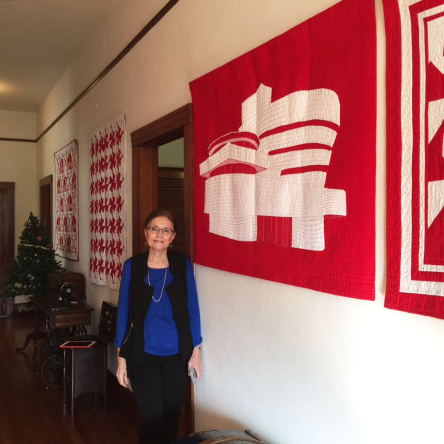 Judy Shelton with her Guggenheim  quilt in upstairs hall.jpg