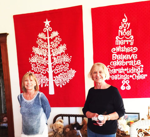Marianne and Louise in front of  Sarah Michaels two Christmas tree quilts in Childrens room.jpg