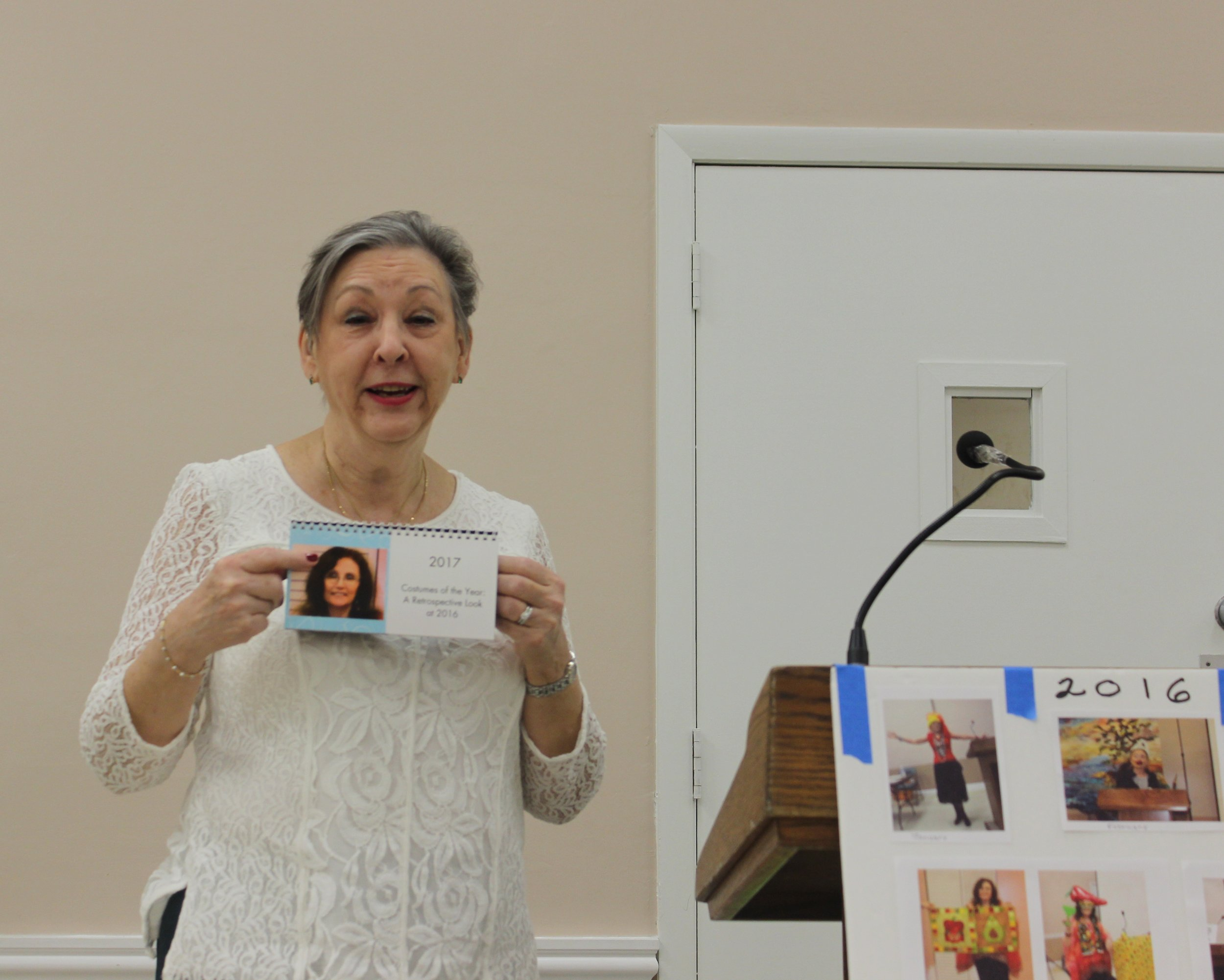 New Prez Christine Franko getting Judy Shelton's 2016 costumes of the month calendar.JPG