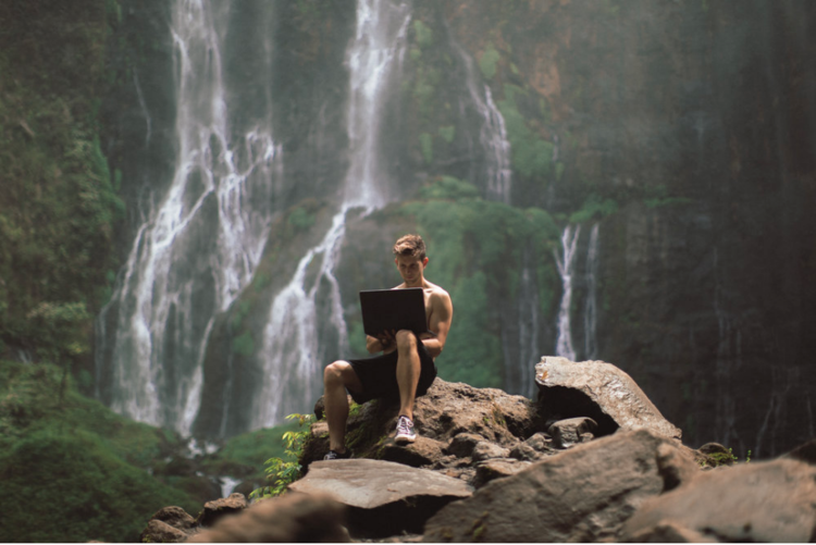Lost LeBlanc on laptop at Tumpak Sewu Waterfall in East Java, Indonesia