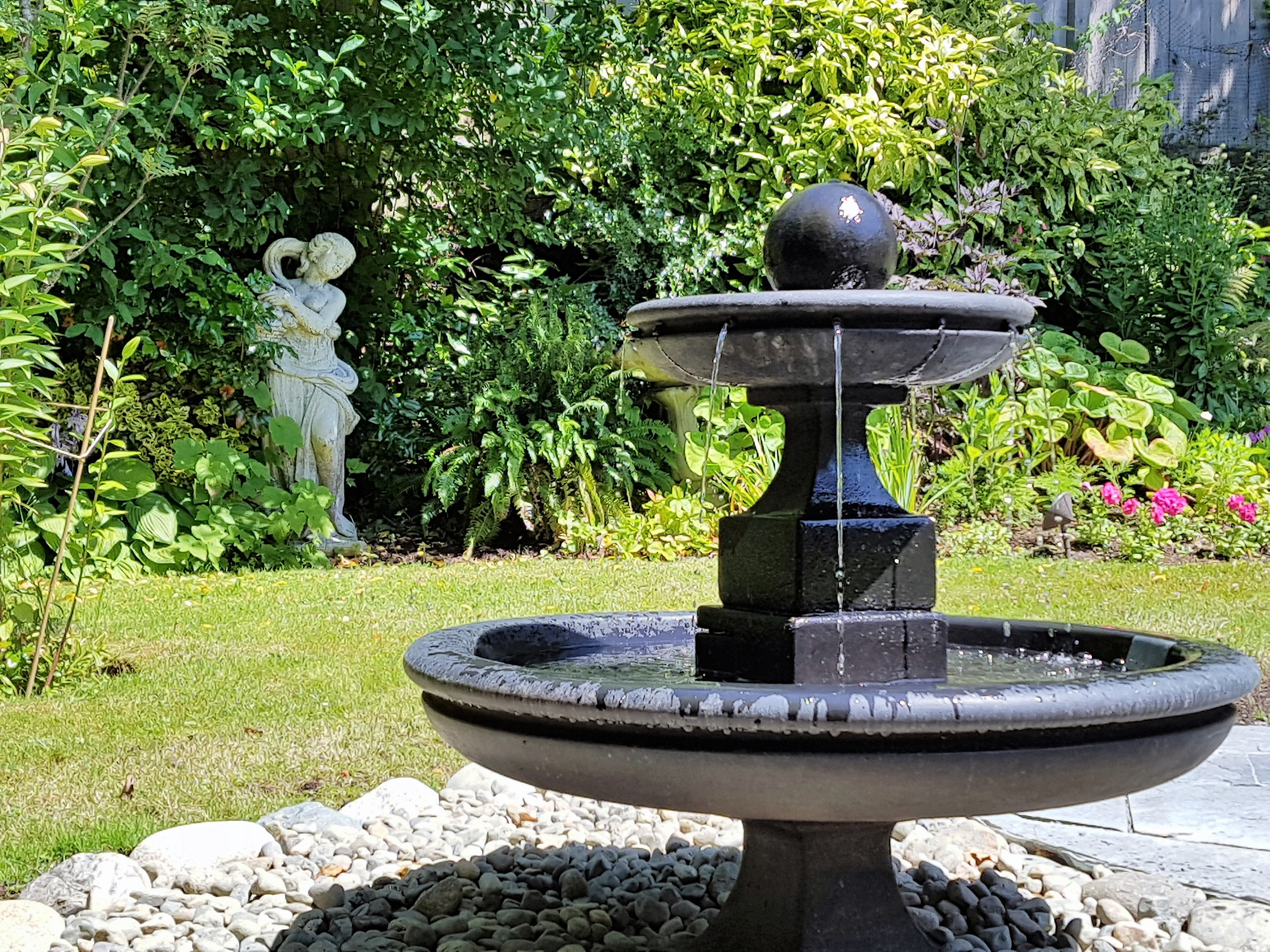 This classic, two-tiered fountain is a study in simplicity. Placed in back third of the yard, on a bed of river rock, it draws they eye to the statue embedded in foliage along the property line.