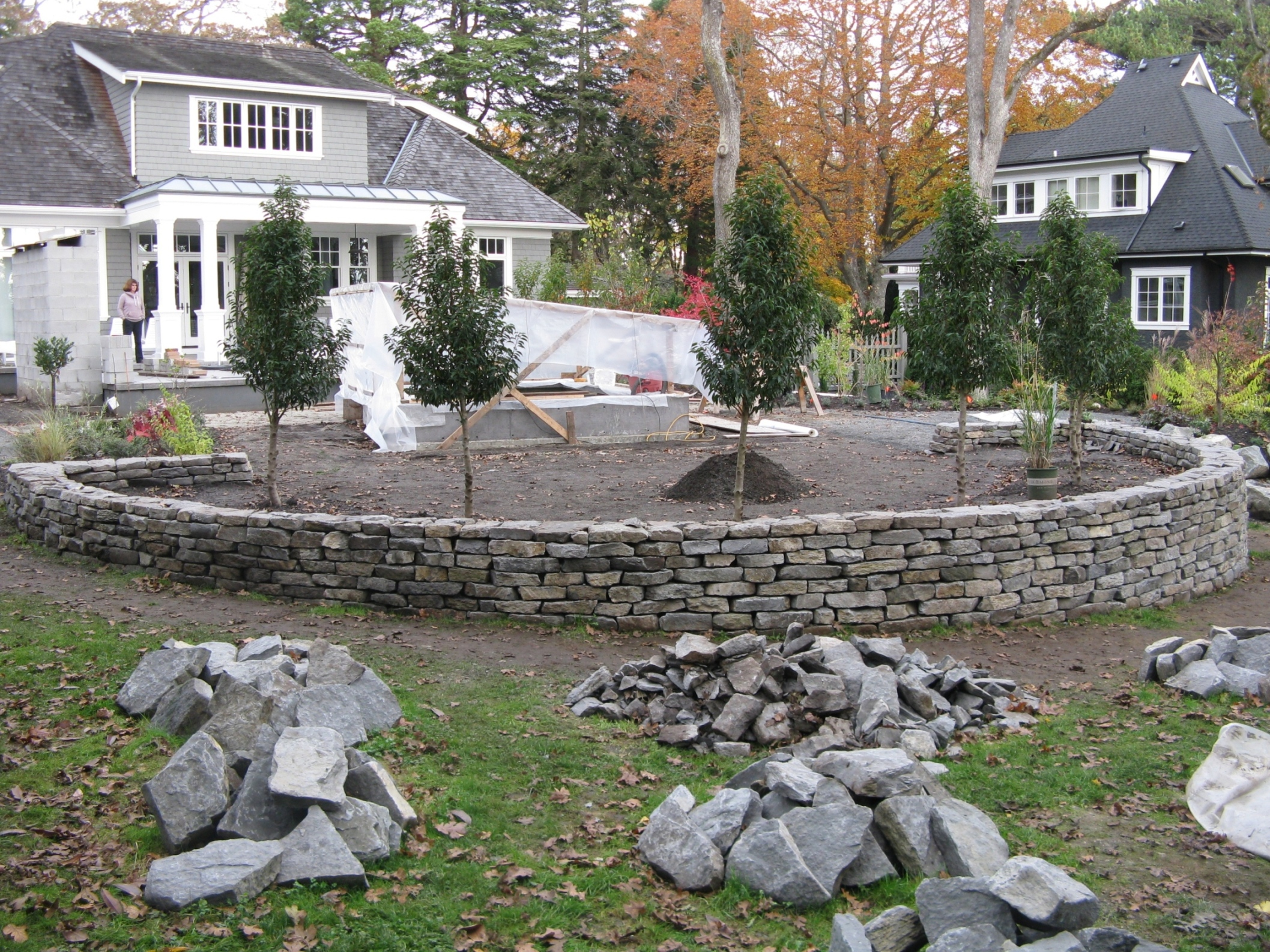 A circular wall of basalt is the central design element in this back yard renovation featuring a spa, outdoor fireplace and new garden