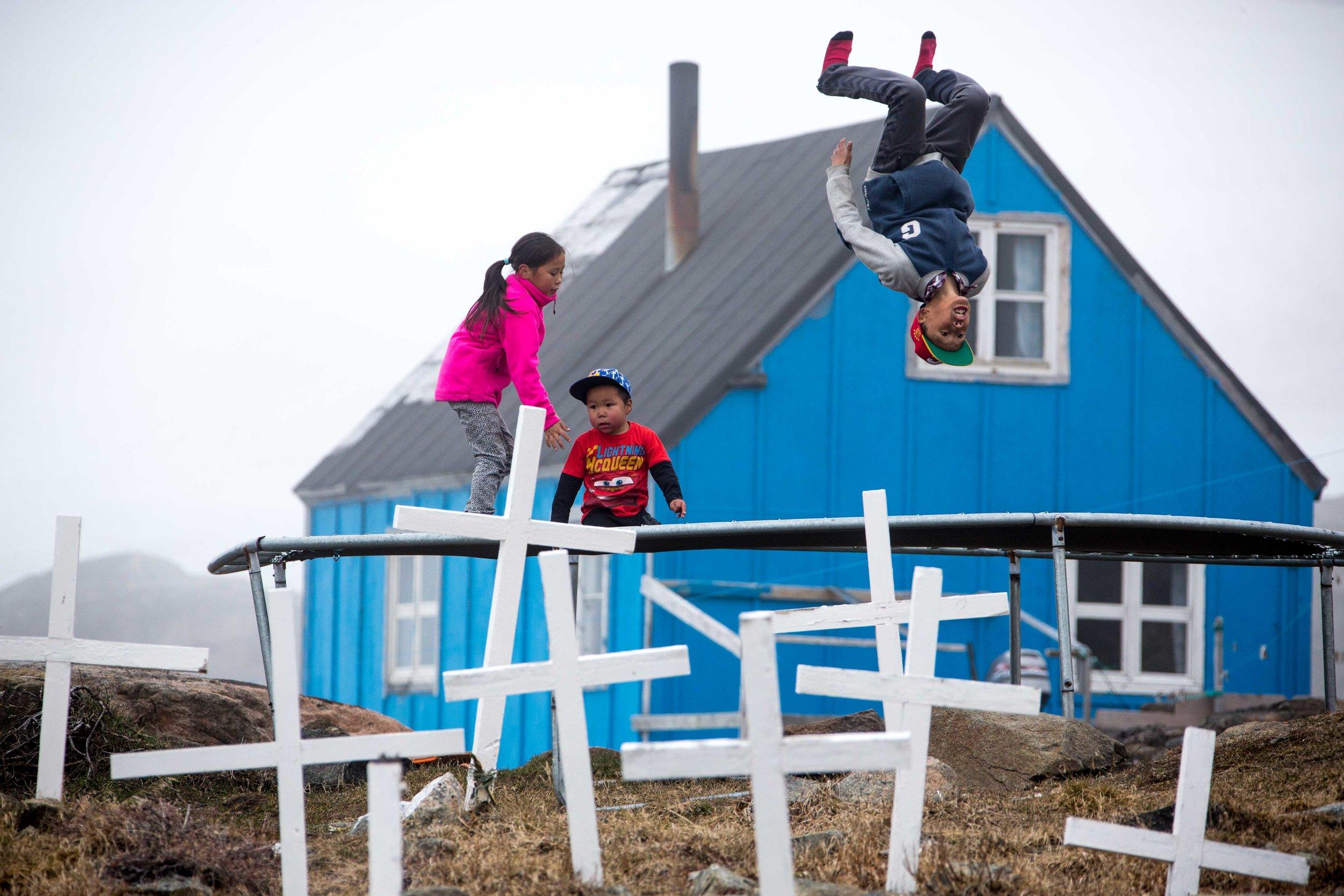 Kids take turns doing backflips on their trampoline next to Kulusuk's cemetary.