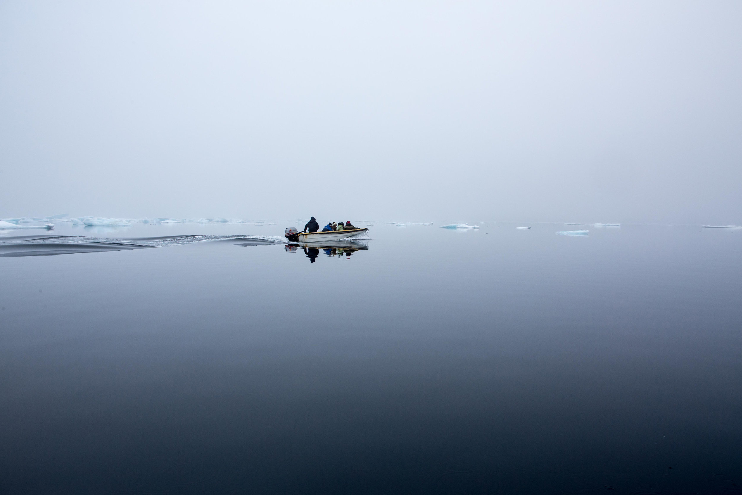 The dingy reaching open water with icebergs behind. East Greenland.