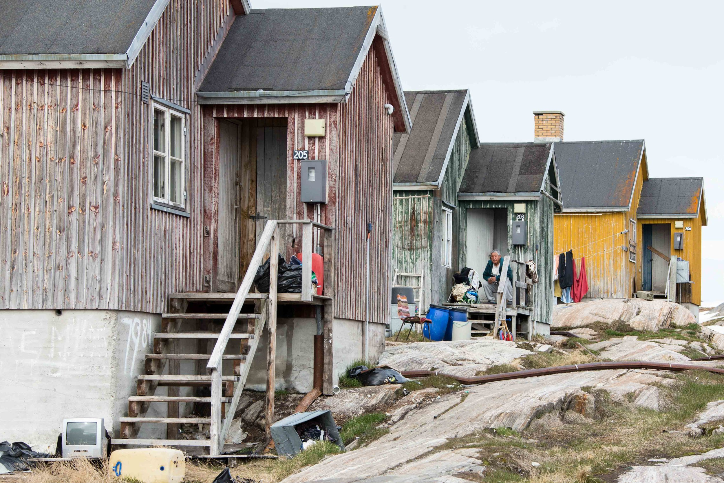 A town elder sits on his porch in Kuummiut, Greenland.