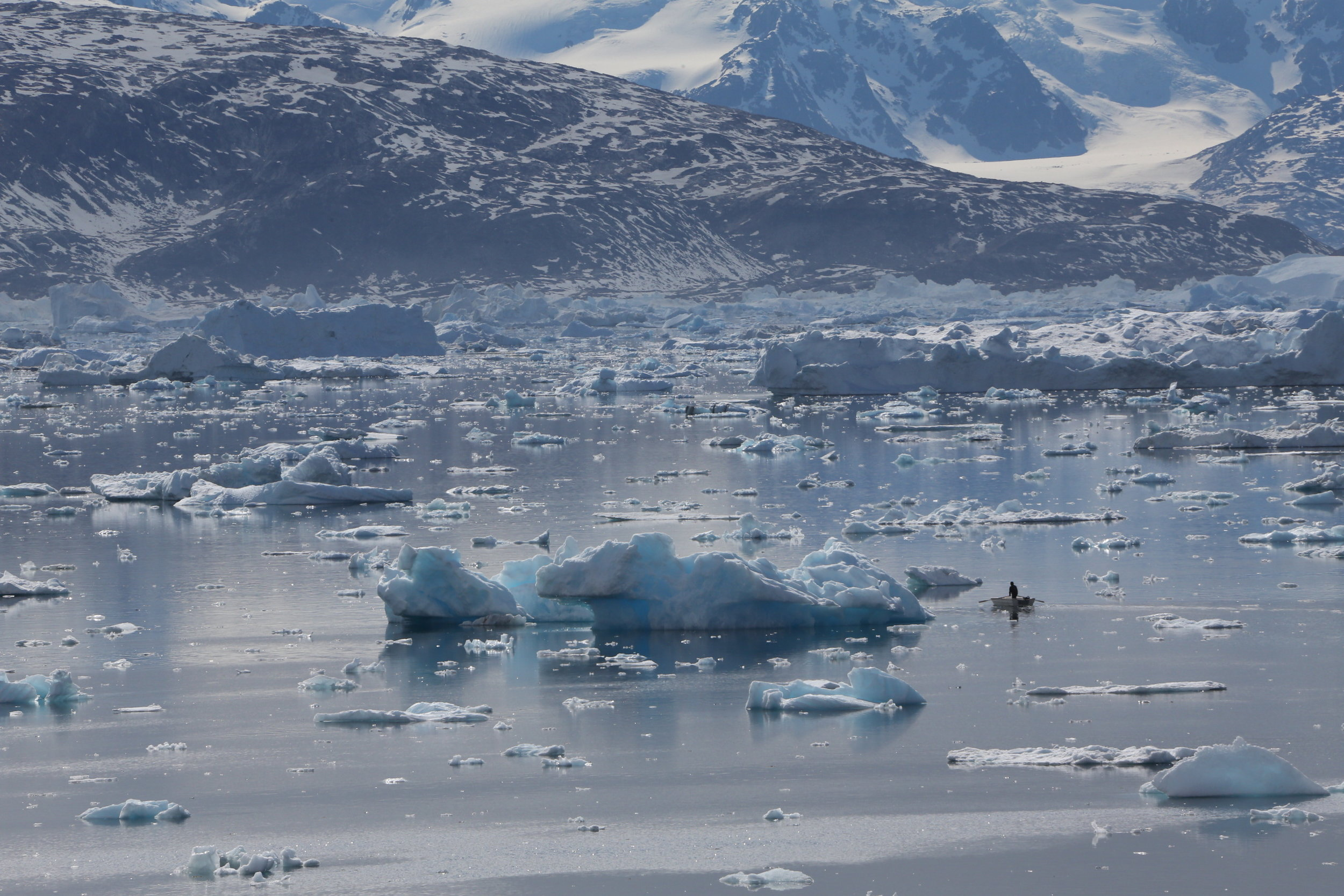 A local hunter takes his boat out amongst the icebergs in the ice fjord. Tinit, Greenland.