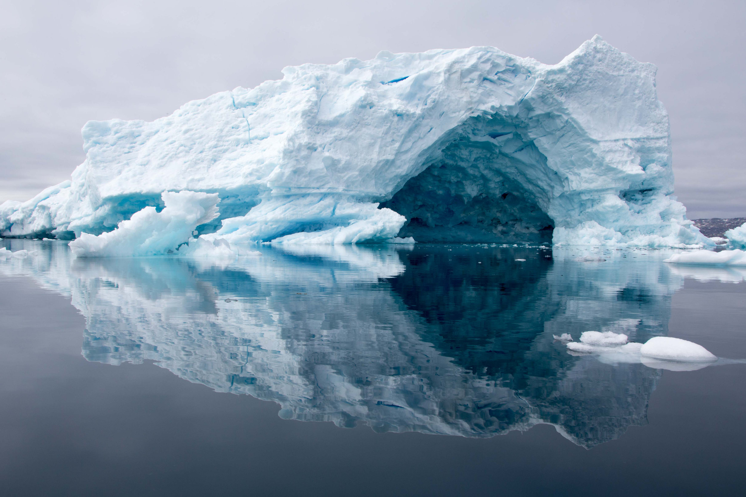 An ice cave formed within an iceberg on the ice fjord in Tinit, Greenland.
