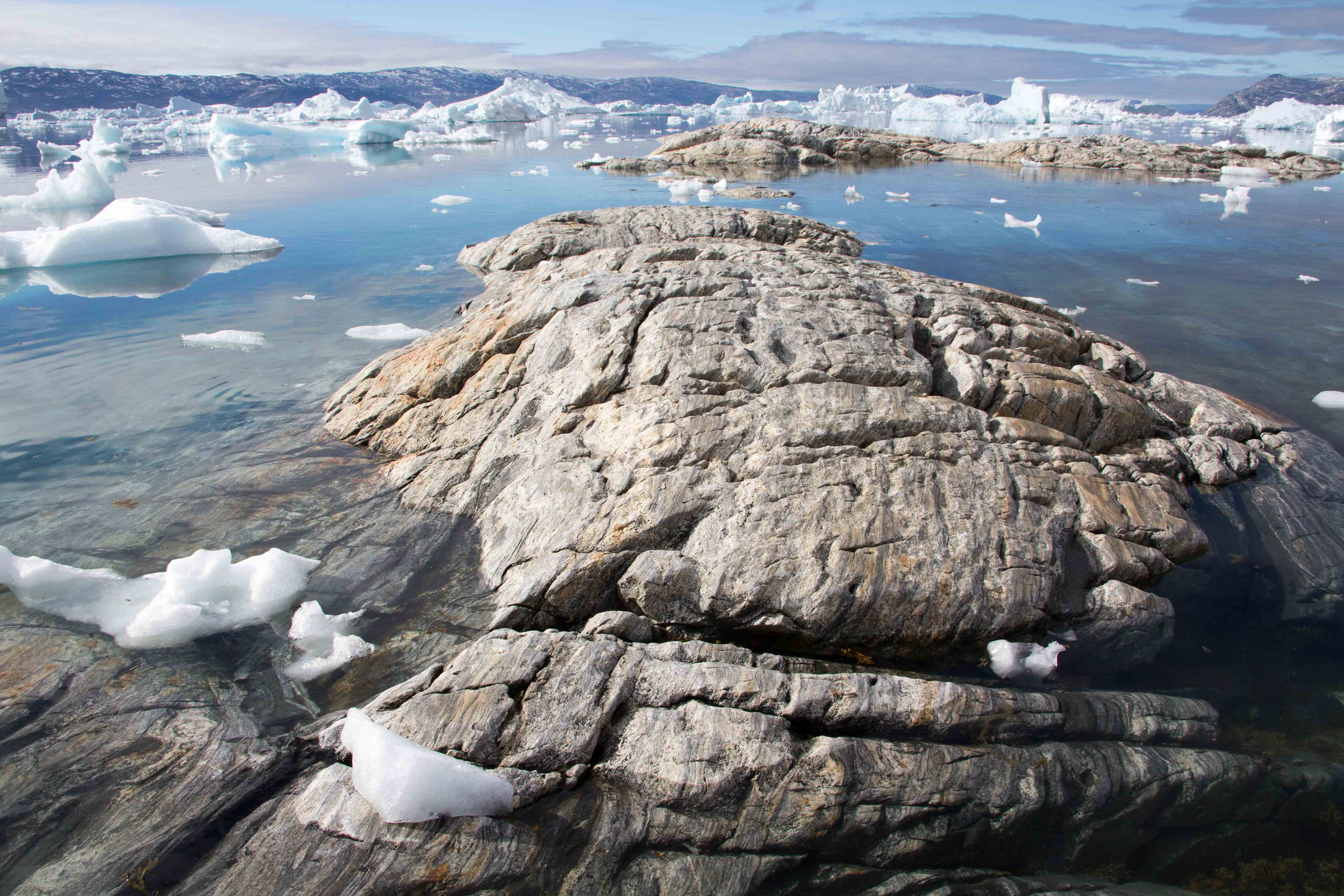 Rocks are exposed at the tide recedes, eventually beaching some of the smaller icebergs. Tinit, Greenland.
