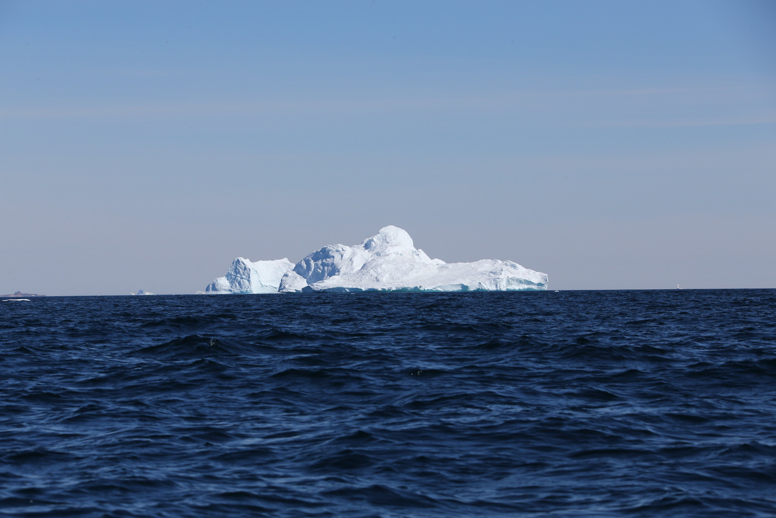 A massive, larger-than-cruise-ship sized iceberg in the sea off the eastern Greenlandic coast.