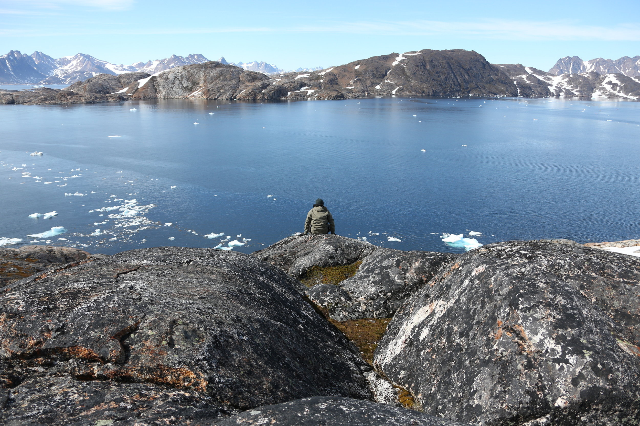 Sitting on the rocks overlooking the water from Kulusuk Island, Greenland.