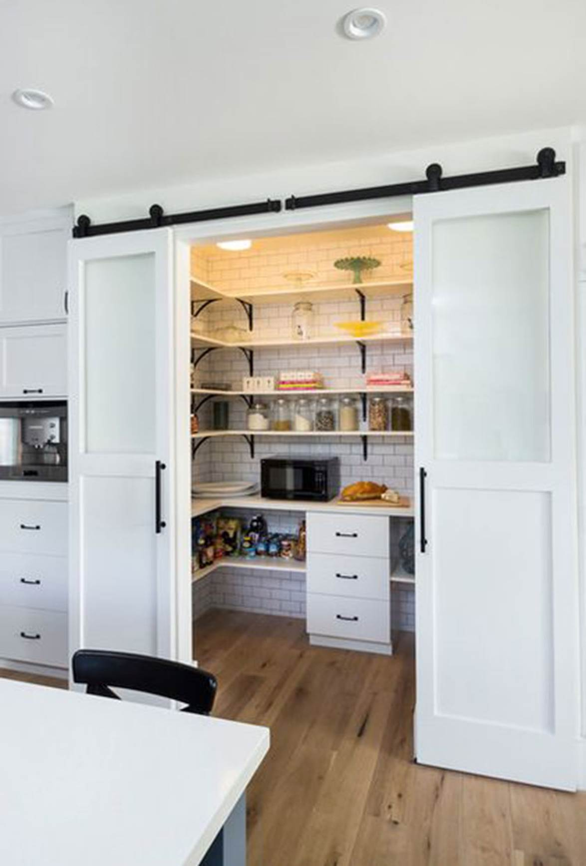 Sliding barn doors are perfect for a farmhouse style kitchen. Why not make them a double and it becomes a nice wide opening with easy access. |  source
