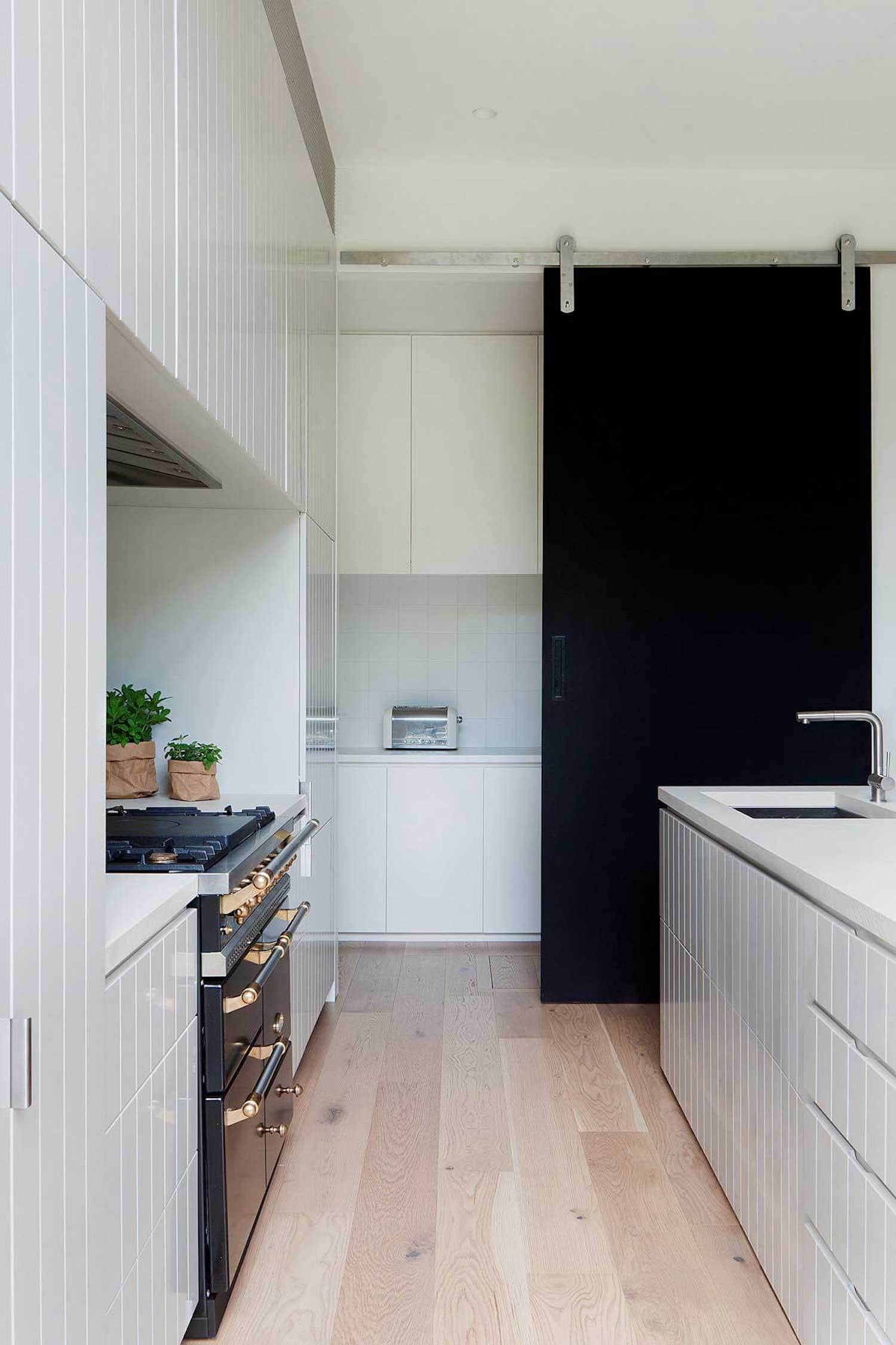 Create impact with a black modern barn door. It's a sharp contrast with an all white colour scheme. | stylist & home owner:  Danika Rehfisch