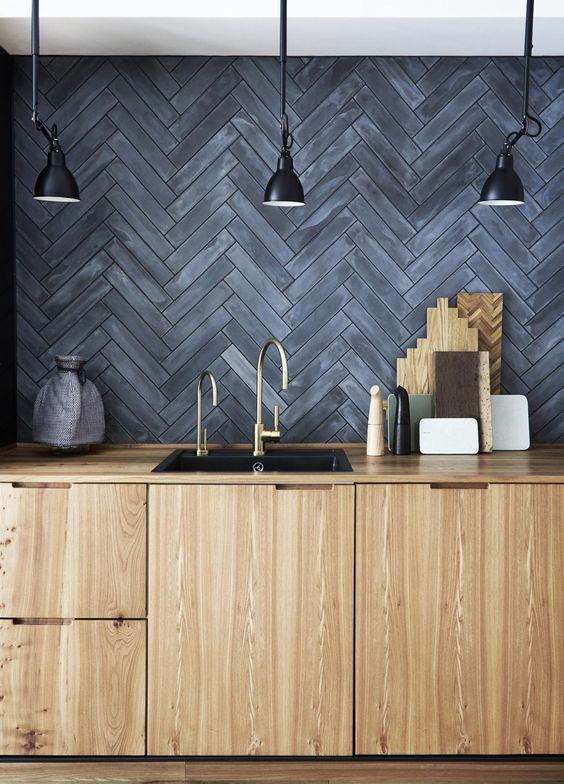 Dark gray, Moroccan cement tiles laid in a herringbone pattern, creates quite a statement in this Copenhagen kitchen. Image credit:  Skona hem
