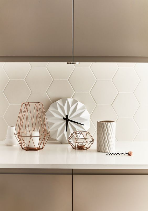 Matte white hexagon tiles adds modern texture to this kitchen.  Image source
