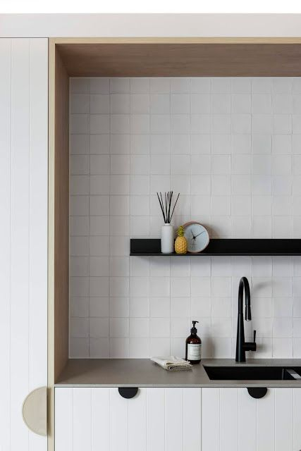 Handmade white butcher tiles in a simple grid pattern, cover many surfaces in this spectacular kitchen. Designed by:  Minosa