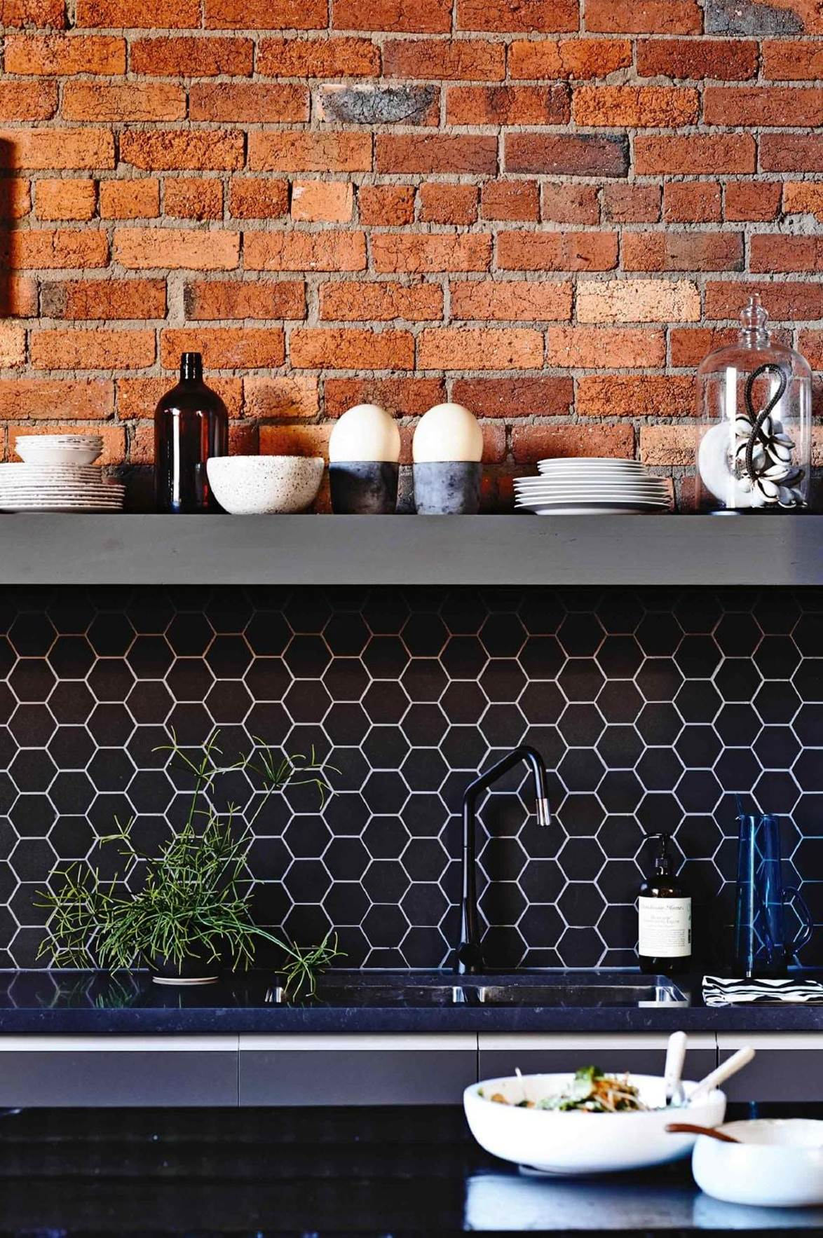 Industrial style kitchen with dark, dramatic tiles. Clever use of white grout to accent the honeycomb pattern. Styled by:  Rachel Vigor