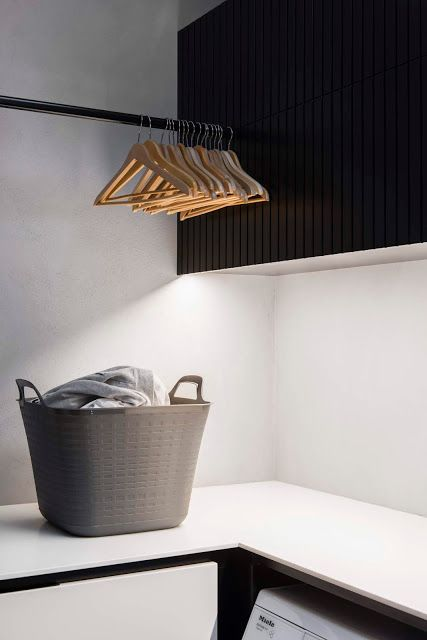 Stylish black hanging rail and great lighting in this modern laundry.    Minosa Design