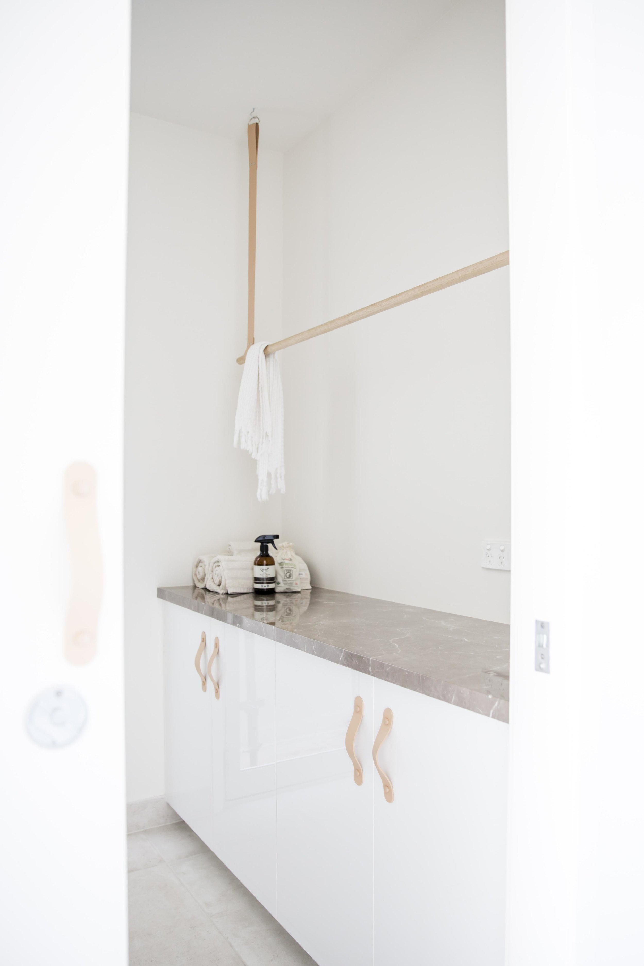 Nude leather and oak rod, hanging from the ceiling, Australian designed product.    H&G Designs