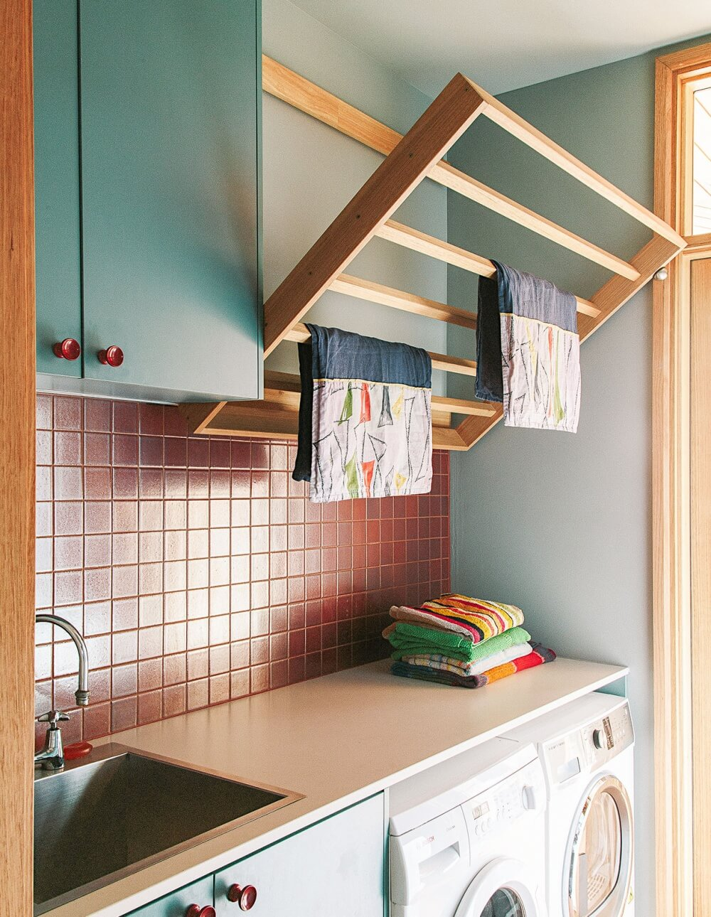 Fabulous use of colour and timber in this retro style laundry, featuring a tilt out drying rack.    Brave New Eco