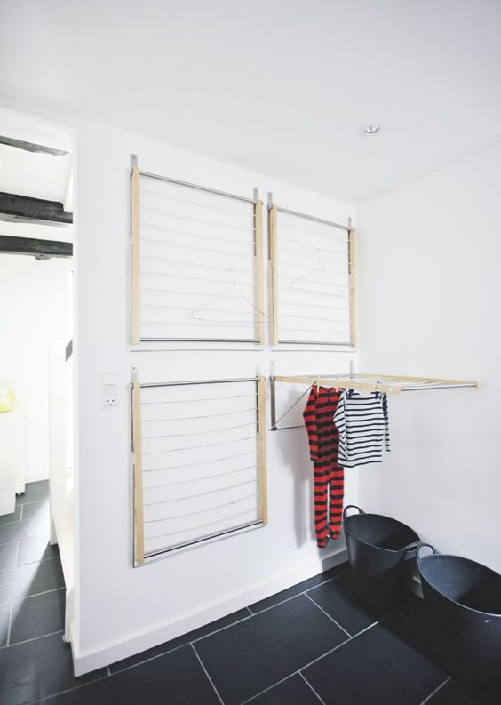 Several wall mounted drying racks in this Scandinavian laundry room are very practical.    Bolig Magasinet