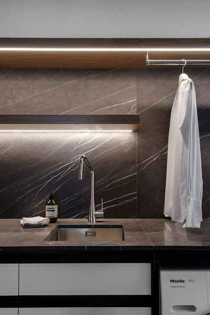 A laundry with moody colour palette and glorious strip lighting.    Minosa Design