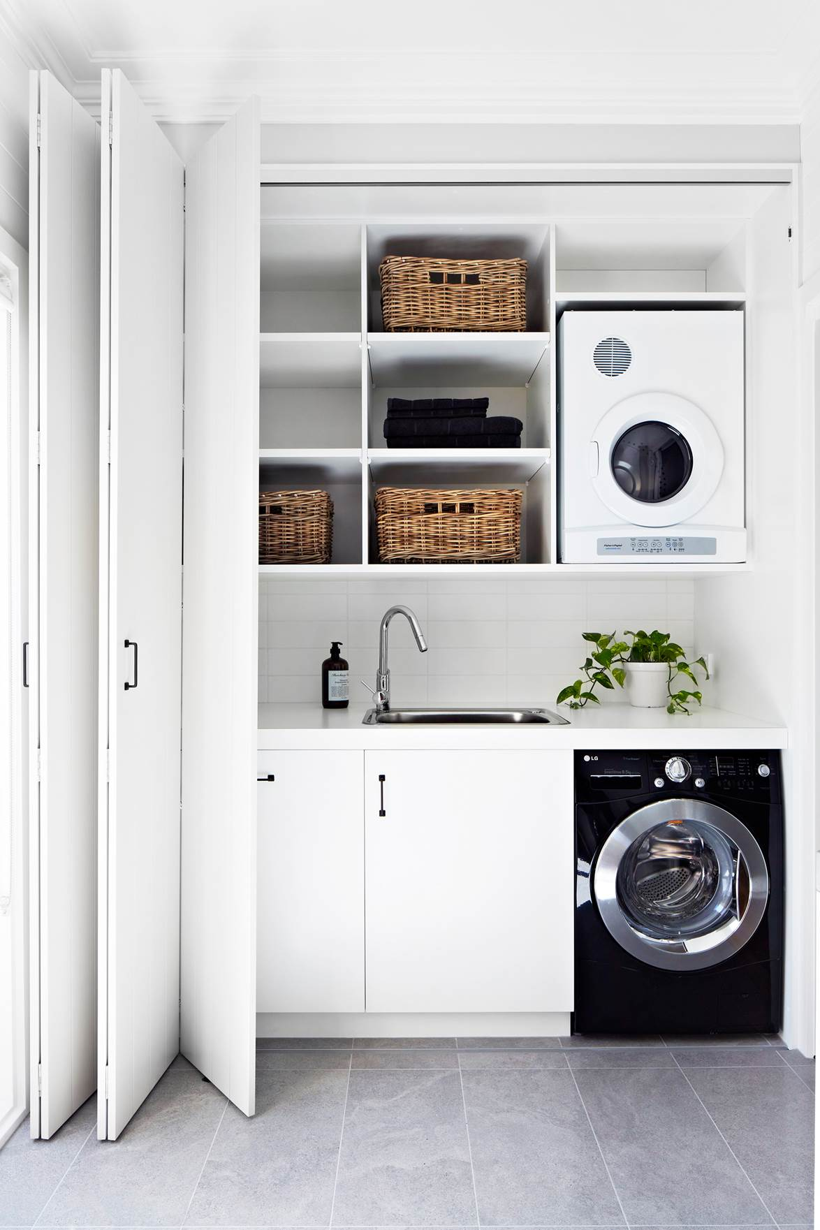 This simple laundry has a spacious benchtop, and it all hides behind bifold doors. | interior design:  Bloom Interior Design & Decoration