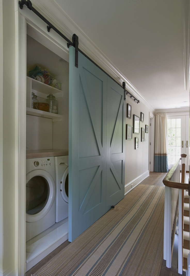 Another blue barn door covering a laundry nook in the hallway, love this. | design:  Brooks & Falotico