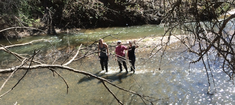 Linda Birdsong, flanked by two students, place leaf packs in Salem Creek.