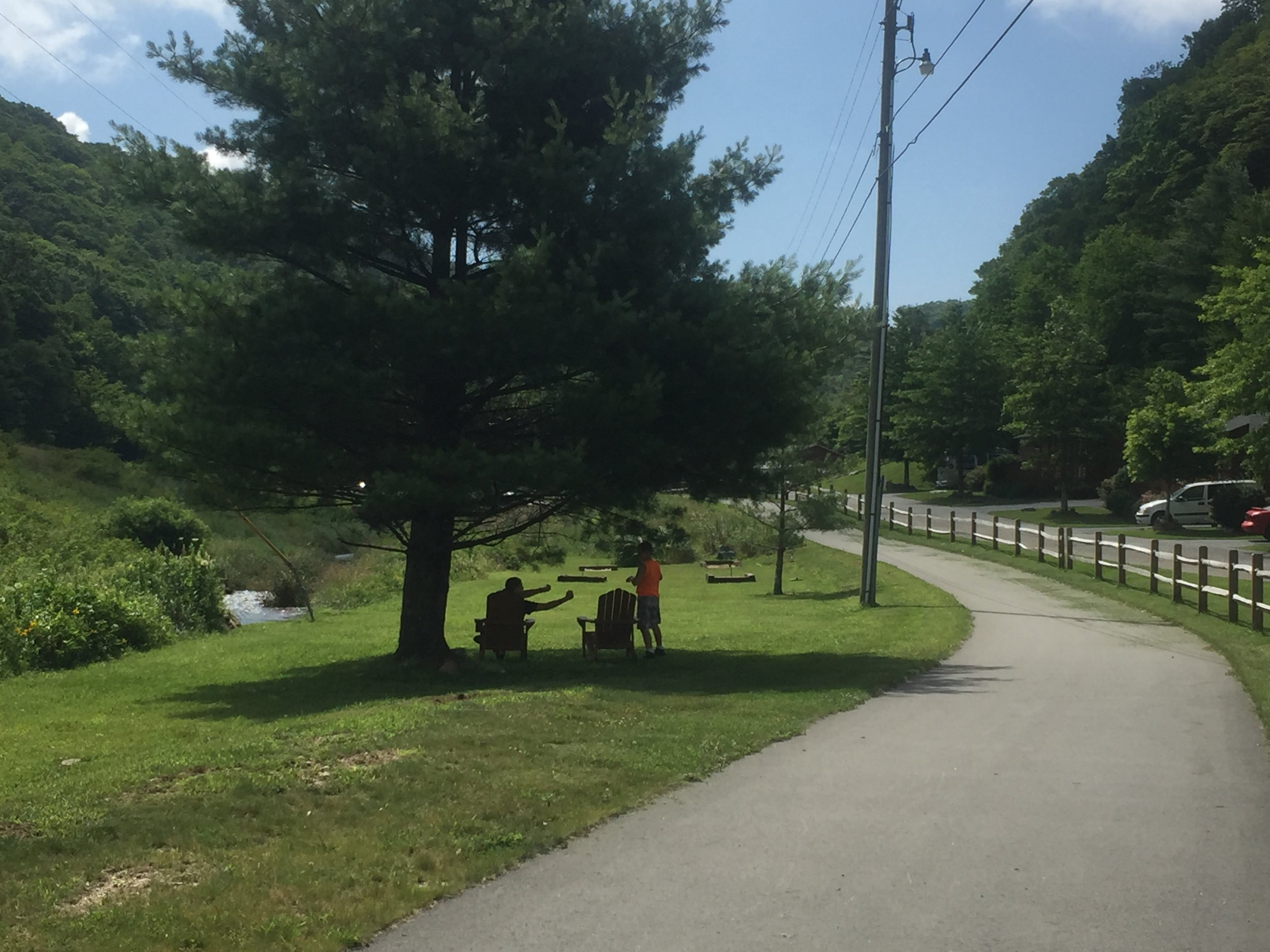 Folks enjoying the shade on the Middle Fork Greenway in front of Riverside log cabins at Mystery Hill.