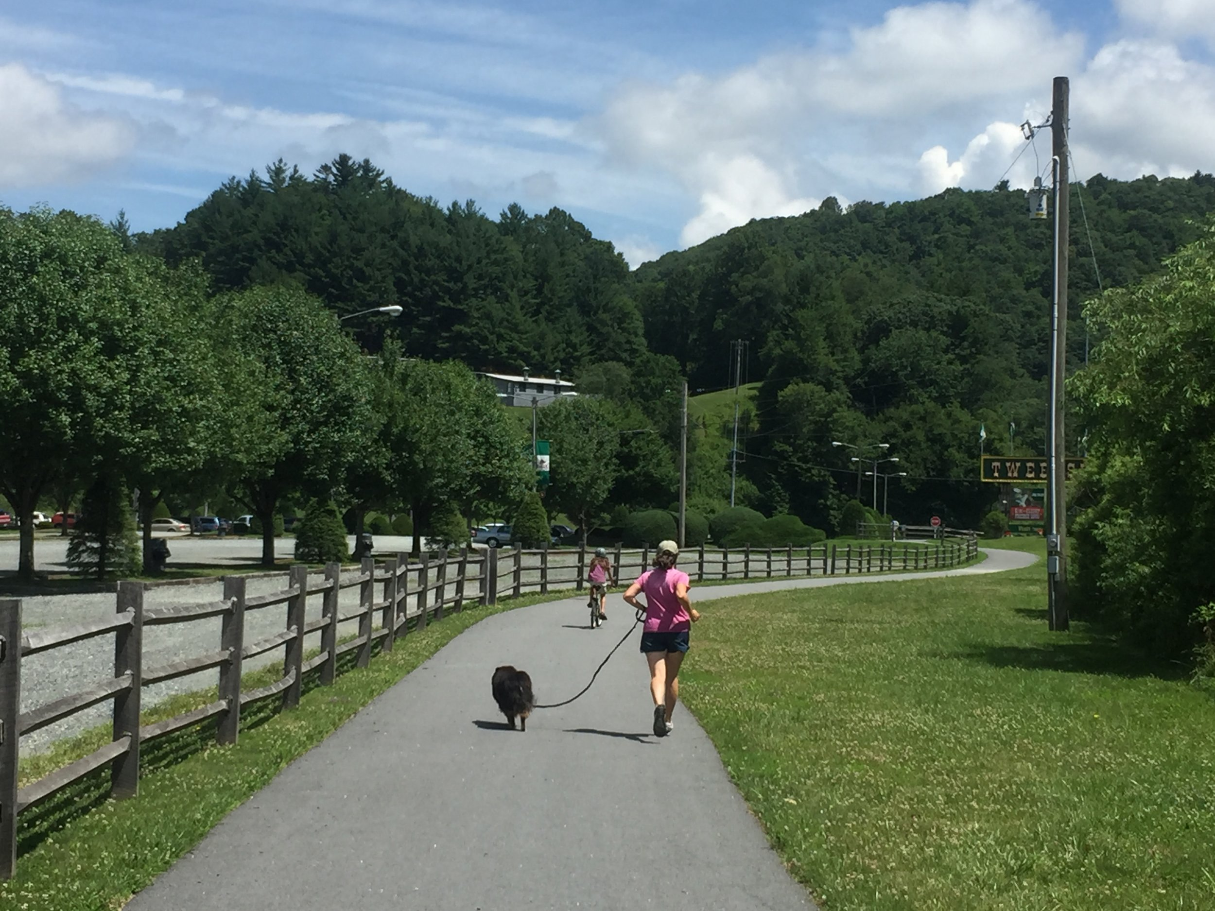 Joggers and cyclists using the Middle Fork Greenway in front of Tweetsie Railroad.
