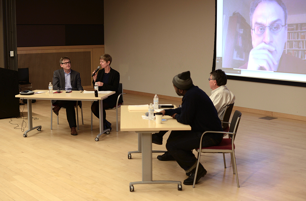 """""""The Artist as Entrepreneur,"""" a panel discussion held on February 9, 2017, at the Maryland Institute College of Art. From left, Paul Jaskunas (moderator), Stacey Salazar, Lewis Hyde, and Paul Rucker. On screen, participating remotely, William Deresiewicz. Photograph by Wen Li."""