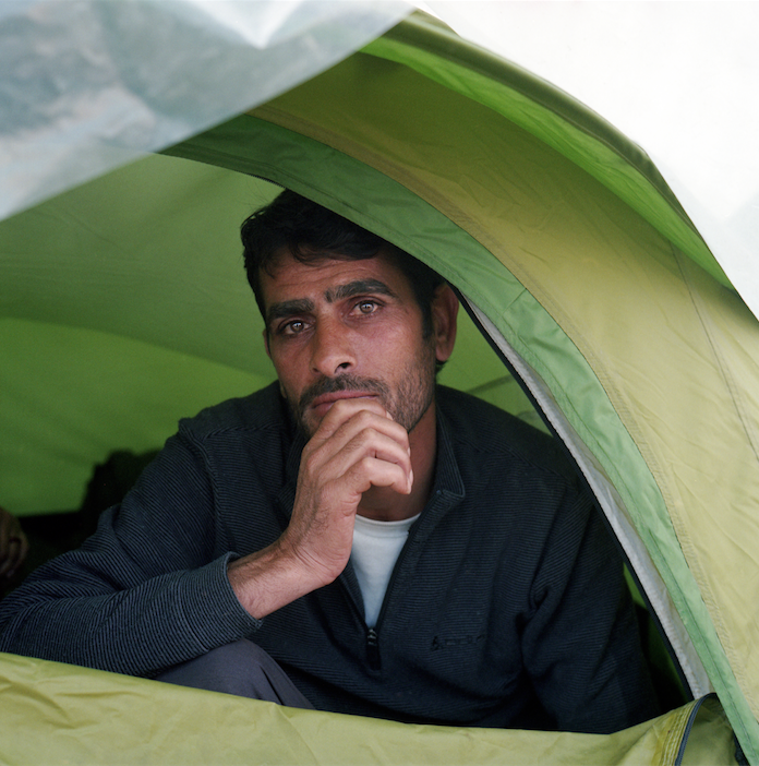 Syrian refugee inside his tent in Idomeni, Greece. March 2016. Photograph by Rena Effendi.
