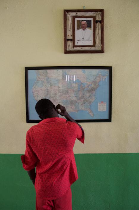 A Haitian migrant beneath a photograph of Pope Francis at the Casa del Migrante.