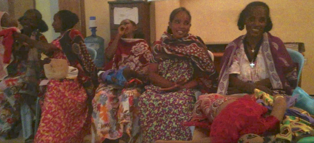 Women who have recently been cured of obstetric fistula at the Healing Hands of Joy, examining Protect Your Sister Project's educational tools and having a good laugh.