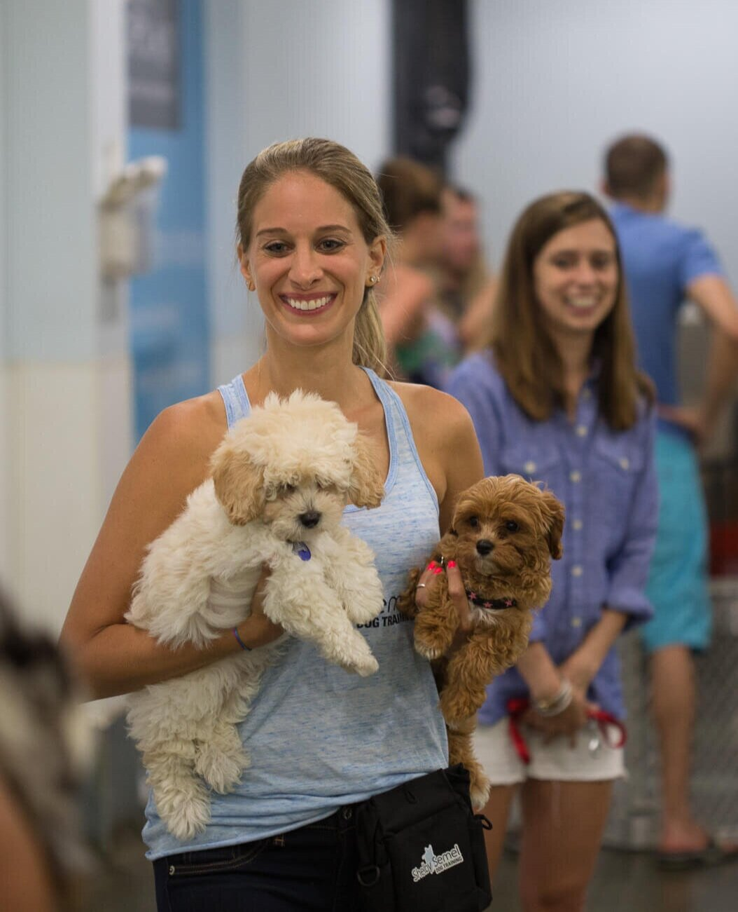 Shelby Semel holding two puppies in a group class