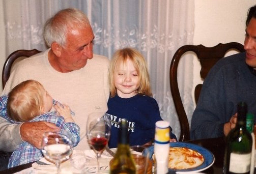"""Ray Federman gently tells an after dinner story to tiny Quentin Joyce and Anna Livia. """"If a word does not exist,"""" he tells them, """"you can invent it."""""""