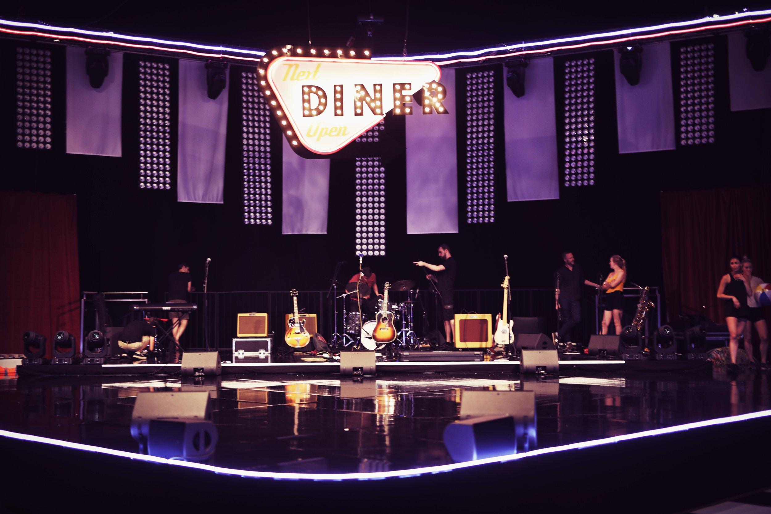 The Fifties-styled stage at the NEC Birmingham. The Bluejays set up beneath a neon Diner sign, July 2019