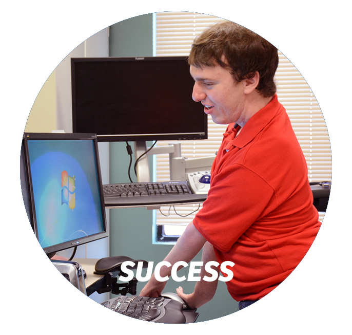 Young adult man wearing red shirt with a physical disability standing in front of workstation that has been modified with assistive technology.