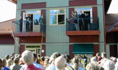 Kungen har gått upp på balkongen för att klippa bandet.