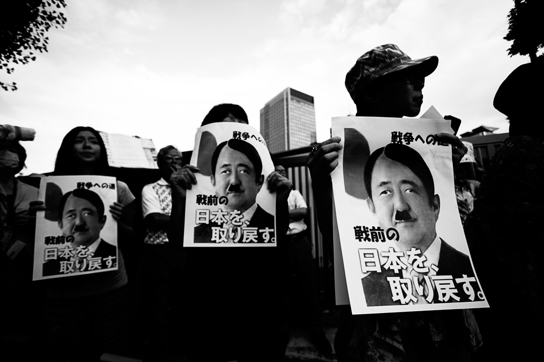 Protesters outside the Diet Building against the self-defense act bill in Tokyo showing Abe picture on Hilter-like looking