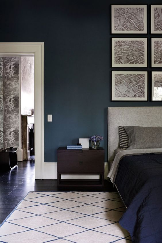 The rich wall colour gives this room depth and the display of maps above the headboard really stand out as a result. The dark floor and bedspread ground the wall colour, while the grey headboard, pillows and neutral rug unify the maps with the rest of the room.