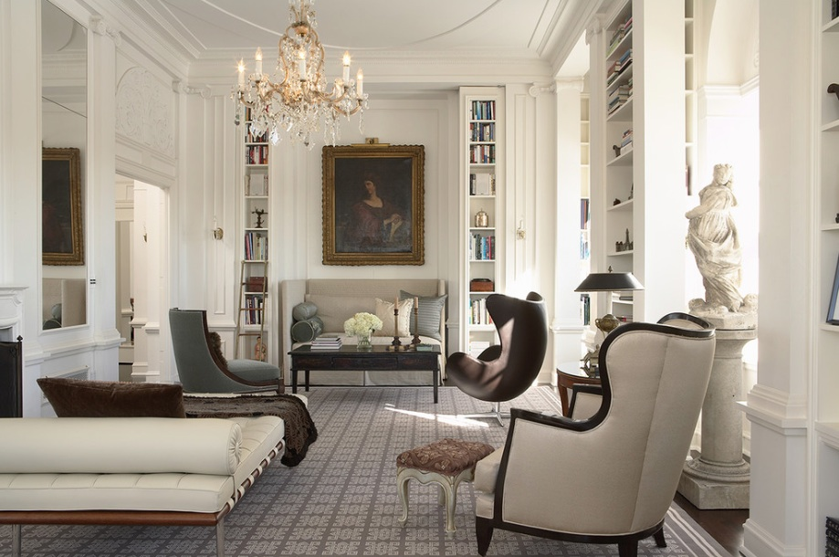 This room beautifully merges classical and modern style. The white statue is prominent, but does not dominate and your eye is first drawn to the painting at the end of the room, as well as the chandelier at the top. This allows the looker to appreciate the size and height of the room. The coffee table, as well as the wood of the furniture is dark, which would be in keeping with Victorian tastes. The light walls provide a perfect backdrop to help the furniture and accessories stand out in their creams and muted shades. The overall effect is well balanced and comfortable.