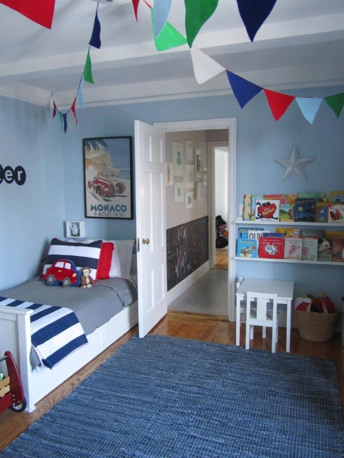 What an inviting room this is! Open shelving, bright cushions, white accessories and the warm wood floor peeping from beneath the rug lift the room and make it fun and appealing. A lovely shade of blue on the walls.   Photo: projectnursery.com