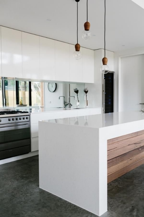 Check out the mirrored splash back! It's looks more like a window and really draws you into the space. Mirrors can so easily be incorporated into the kitchen. If you are worried about maintenance though and keeping it all shiny and clean, a tarnished, antique mirror would help with this and also add extra beauty to your kitchen.   Image: style-files.com